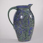 This is a pitcher with a blue and green wax resisit pattern in the glaze.Pitchers like this cost $60.00